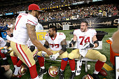 Colin Kaepernick of the San Francisco 49ers talks with Mike Iupati and Joe Staley during the game against the New Orleans Saints at the MercedesBenz...