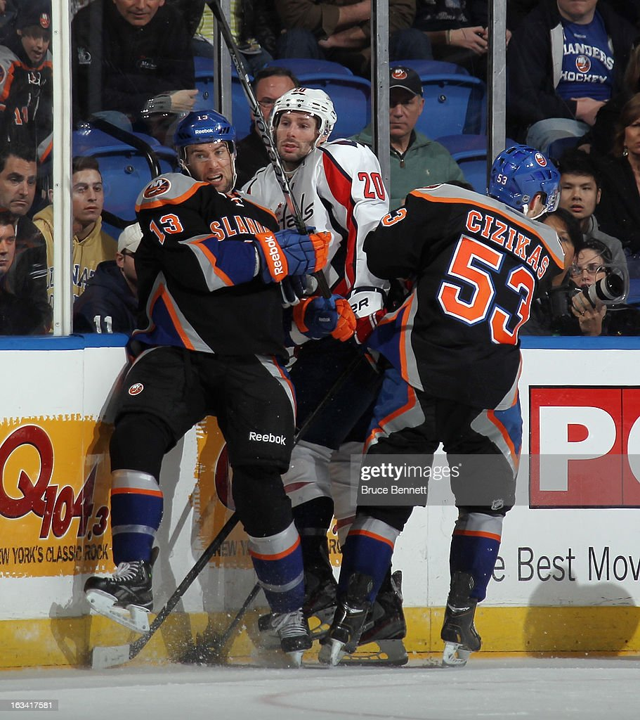 Colin McDonald #13 and Casey Cizikas #53 of the New York Islanders combine on a hit to Troy Brouwer #20 of the Washington Capitals at the Nassau Veterans Memorial Coliseum on March 9, 2013 in Uniondale, New York.