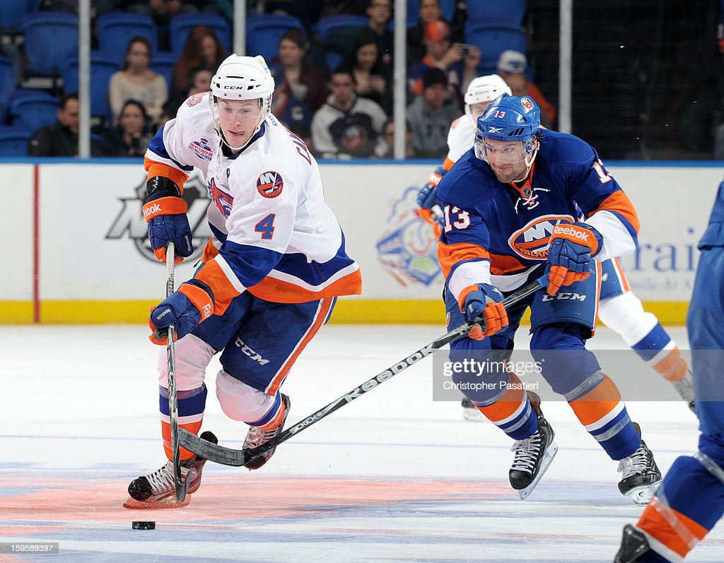 Colin McDonald #13 of Team Blue reaches for the puck against Scott Campbell #4 of Team White during a scrimmage match between players of the New York Islanders and Bridgeport Sound Tigers on January 16, 2013 at Nassau Veterans Memorial Coliseum in Uniondale, New York.