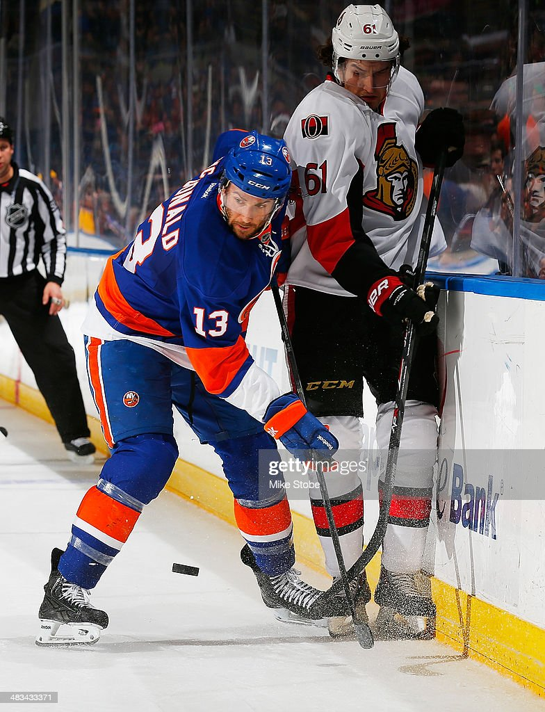 Colin McDonald #13 of the New York Islanders and Mark Stone #61 of the Ottawa Senators battle at the boards for a loose puck at Nassau Veterans Memorial Coliseum on April 8, 2014 in Uniondale, New York.