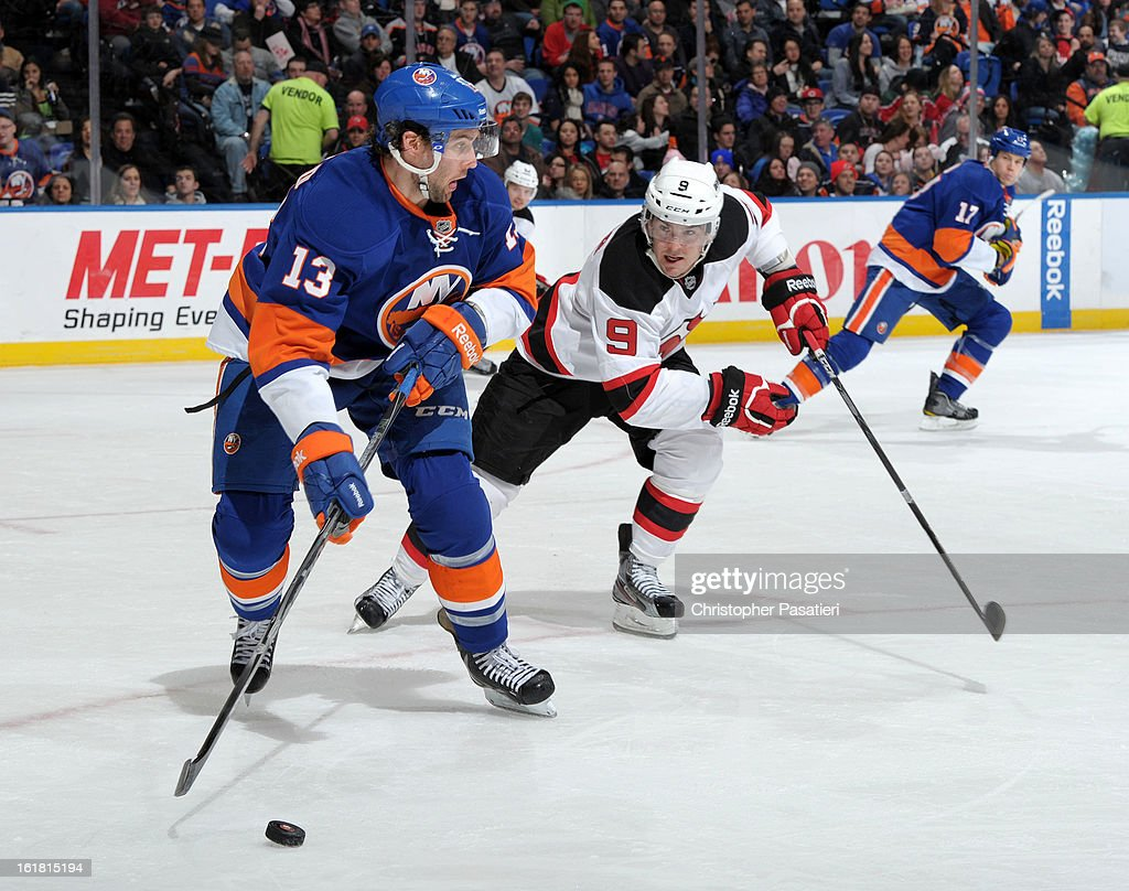 Colin McDonald #13 of the New York Islanders is challenged for the puck by Bobby Butler #9 of the New Jersey Devils during the game on February 16, 2013 at Nassau Veterans Memorial Coliseum in Uniondale, New York.