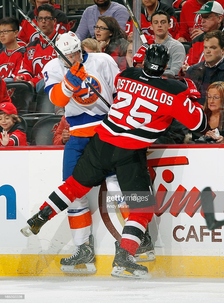 Colin McDonald #13 of the New York Islanders is checked into the boards by Tom Kostopoulos #25 of the New Jersey Devils during the game at the Prudential Center on April 1, 2013 in Newark, New Jersey.