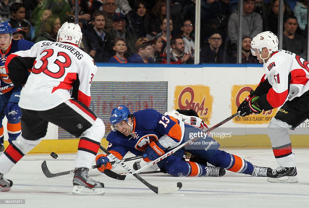 Colin McDonald #13 of the New York Islanders reaches to get the puck out of his zone against the Ottawa Senators at the Nassau Veterans Memorial Coliseum on March 19, 2013 in Uniondale, New York. The Senators defeated the Isalnders 5-3.