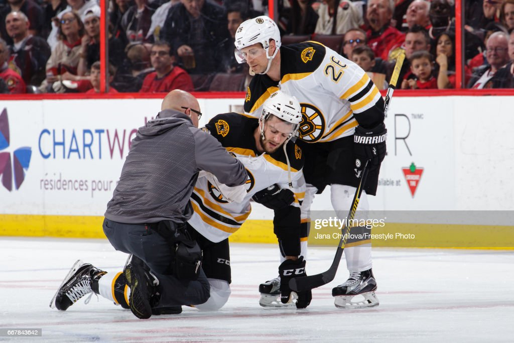 Colin Miller #6 of the Boston Bruins is helped by teammate John-Michael Liles #26 and by the team trainer after bein tripped by Mark Borowiecki (not shown) of the Ottawa Senators in the second period in Game One of the Eastern Conference First Round during the 2017 NHL Stanley Cup Playoffs at Canadian Tire Centre on April 12, 2017 in Ottawa, Ontario, Canada.