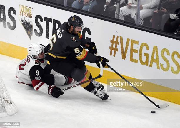 Colin Miller of the Vegas Golden Knights skates with the puck behind the net against Clayton Keller of the Arizona Coyotes during the Golden Knights'...