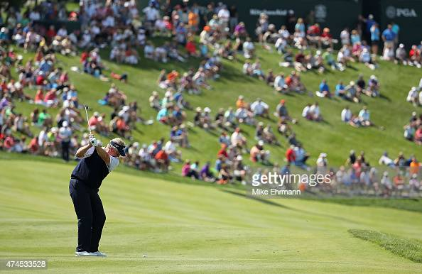 Colin Montgomerie of Scotland hits his approach shot on the 18th hole during the third round of the 2015 Senior PGA Championship Presented By...