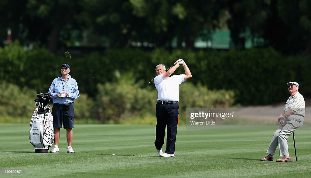 Colin Montgomerie of Scotland is watched by his father, James during a practice round ahead of the Omega Dubai Desert Classic on January 29, 2013 in Dubai, United Arab Emirates.