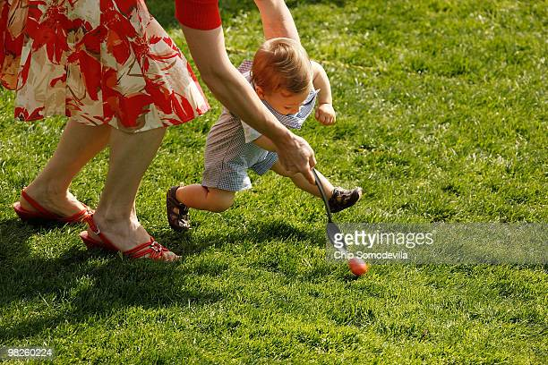 Colin Moorhouse 10 months of Atlantic City New Jersey gets a little help from his mother Megan Moorhouse during the Easter Egg Roll at the White...
