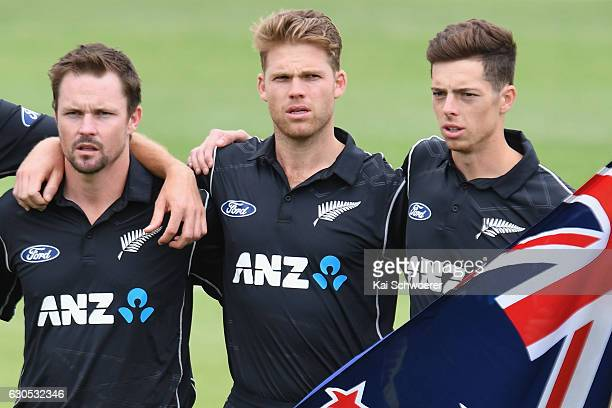 Colin Munro Lockie Ferguson and Mitchell Santner of New Zealand line up for their national anthem during the first One Day International match...