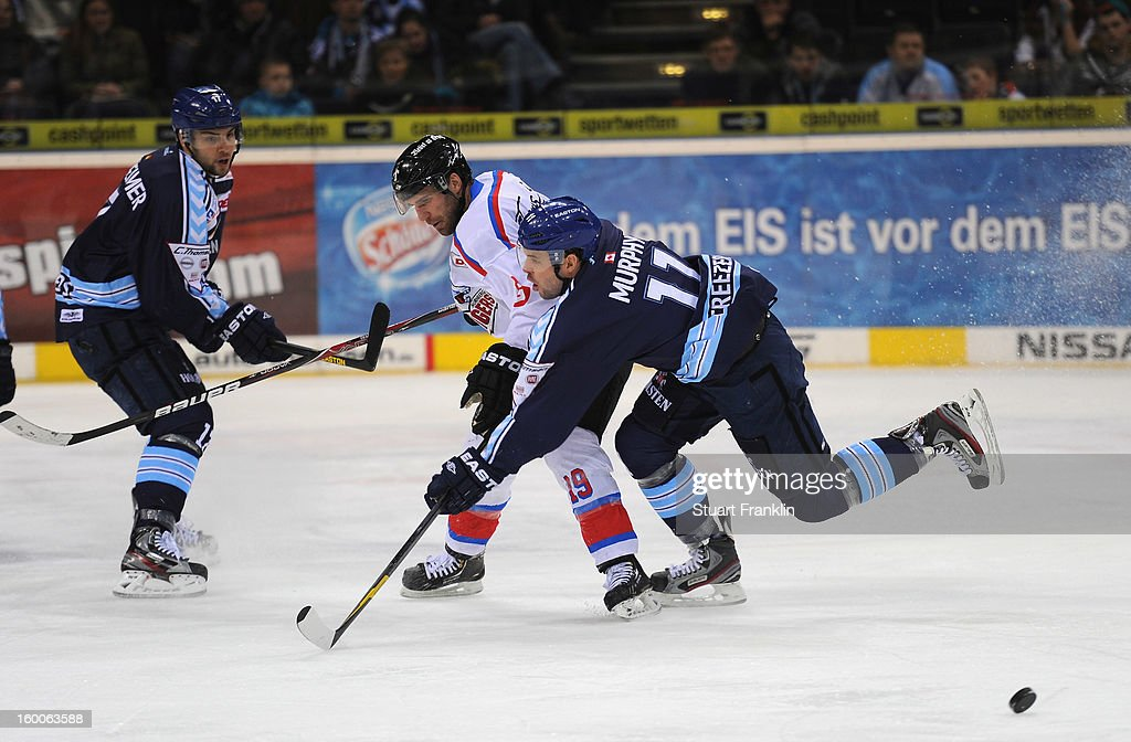 Colin Murphy of Hamburg is challenged by Jason Jaspers of the Ice Tiger during the DEL game between Hamburg Freezers and Thomas Sabo Ice Tigers at O2 World on January 25, 2013 in Hamburg, Germany.