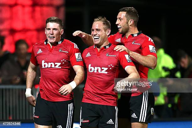Colin Slade Andy Ellis and Tom Taylor of the Crusaders celebrate after scoring a try during the round 13 Super Rugby match between the Crusaders and...