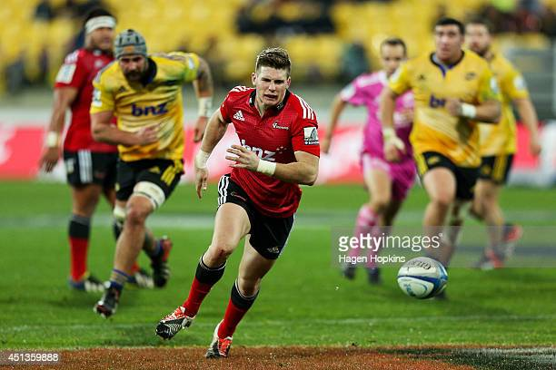 Colin Slade of the Crusaders looks to gather a loose ball during the round 17 Super Rugby match between the Hurricanes and the Crusaders at Westpac...