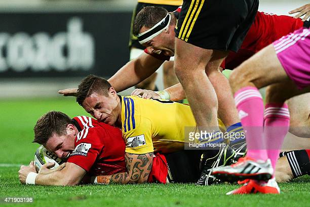 Colin Slade of the Crusaders scores a try in the tackle of TJ Perenara of the Hurricanes during the round 12 Super Rugby match between the Hurricanes...