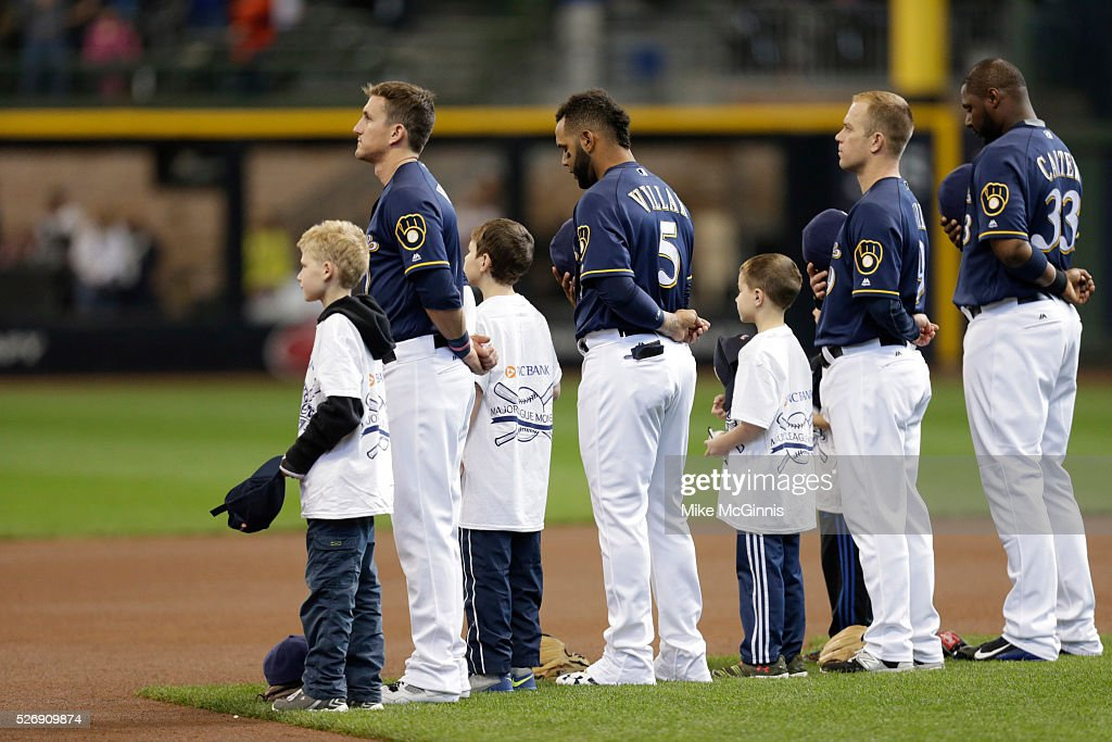 Colin Walsh #7 of the Milwaukee Brewers along with <a gi-track='captionPersonalityLinkClicked' href=/galleries/search?phrase=Jonathan+Villar&family=editorial&specificpeople=8981472 ng-click='$event.stopPropagation()'>Jonathan Villar</a> #5, <a gi-track='captionPersonalityLinkClicked' href=/galleries/search?phrase=Aaron+Hill+-+Baseball+Player&family=editorial&specificpeople=239242 ng-click='$event.stopPropagation()'>Aaron Hill</a> #9 and <a gi-track='captionPersonalityLinkClicked' href=/galleries/search?phrase=Chris+Carter+-+Baseball+Player&family=editorial&specificpeople=2177970 ng-click='$event.stopPropagation()'>Chris Carter</a> #31 stand for the playing of the National Anthem before the game against the Miami Marlins at Miller Park on May 01, 2016 in Milwaukee, Wisconsin.