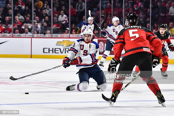 Colin White of Team United States falls as he skates the puck against Thomas Chabot of Team Canada during the 2017 IIHF World Junior Championship...