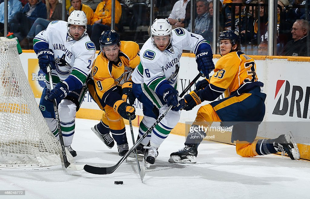 Colin Wilson #33 and Filip Forsberg #9 of the Nashville Predators battle for the puck against Dan Hamhuis #2 and Yannick Weber #6 of the Vancouver Canucks during an NHL game at Bridgestone Arena on March 31, 2015 in Nashville, Tennessee.