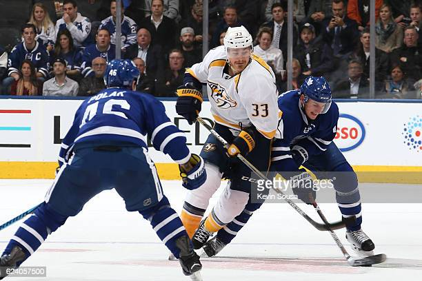 Colin Wilson of the Nashville Predators and Zach Hyman of the Toronto Maple Leafs battle for the puck during the first period at the Air Canada...