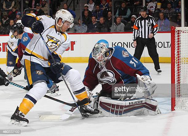 Colin Wilson of the Nashville Predators battles for the puck against goaltender Calvin Pickard of the Colorado Avalanche at the Pepsi Center on...