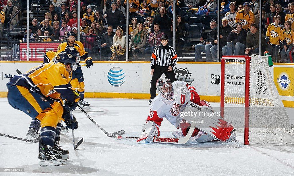Colin Wilson #33 of the Nashville Predators gets the puck in the net for the game winning goal against <a gi-track='captionPersonalityLinkClicked' href=/galleries/search?phrase=Jimmy+Howard&family=editorial&specificpeople=2118637 ng-click='$event.stopPropagation()'>Jimmy Howard</a> #35 of the Detroit Red Wings at Bridgestone Arena on December 30, 2013 in Nashville, Tennessee.