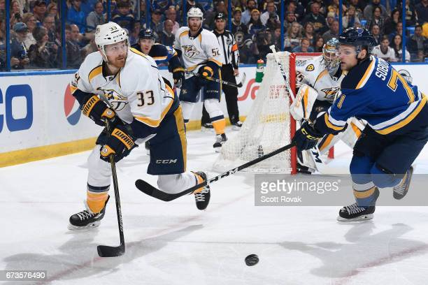 Colin Wilson of the Nashville Predators passes the puck as Vladimir Sobotka of the St Louis Blues pressures in Game One of the Western Conference...
