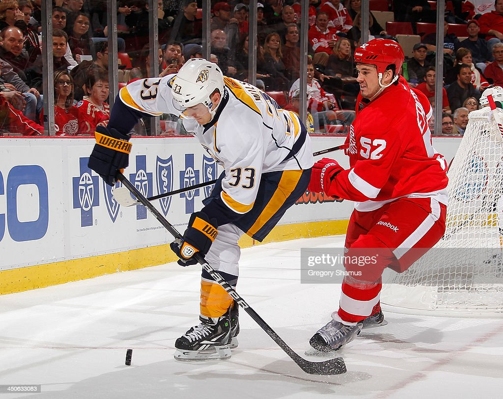 Colin Wilson #33 of the Nashville Predators tries to gain control of the puck in front of Jonathan Ericsson #52 of the Detroit Red Wings during the second period at Joe Louis Arena on November 19, 2013 in Detroit, Michigan.
