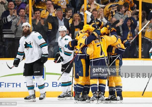 Colin Wilson Yannick Weber and Matt Irwin of the Nashville Predators celebrate a goal against Brent Burns of the San Jose Sharks during an NHL game...