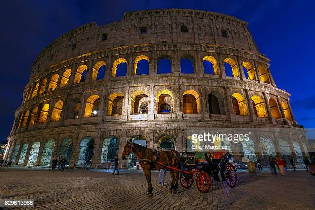 Coliseum Italy in blue hour with a horse cart in front of it