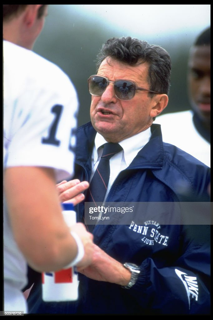 Portrait of Penn St. coach Joe Paterno talking w. QB Kerry Collins #12 on sidelines during game.
