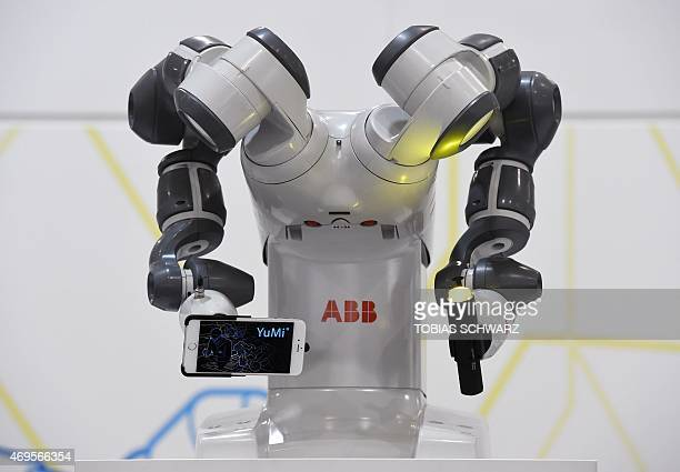 Collaborative dualarm robot YuMi holds a smartphone and a torch at the Swiss automation group ABB booth at the Hannover Messe industrial trade fair...