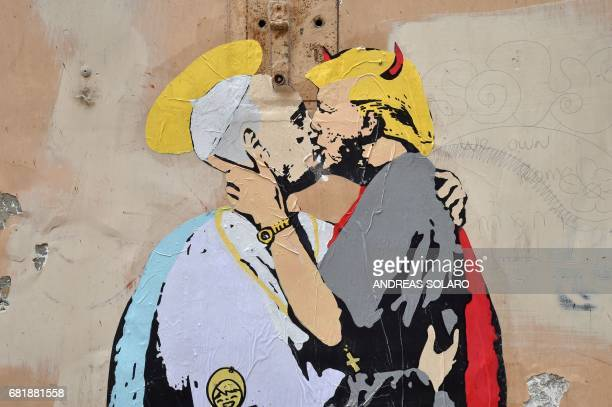 A collage shows Pope Francis kissing US President Donald Trump with a caption by Italian artist TvBoy reading in English and Italian 'The Good...