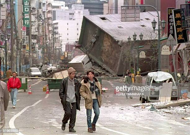 A collapsed building blocks the main street of central Kobe 18 January after a powerful earthquake measuring 72 on the Richter scale struck western...