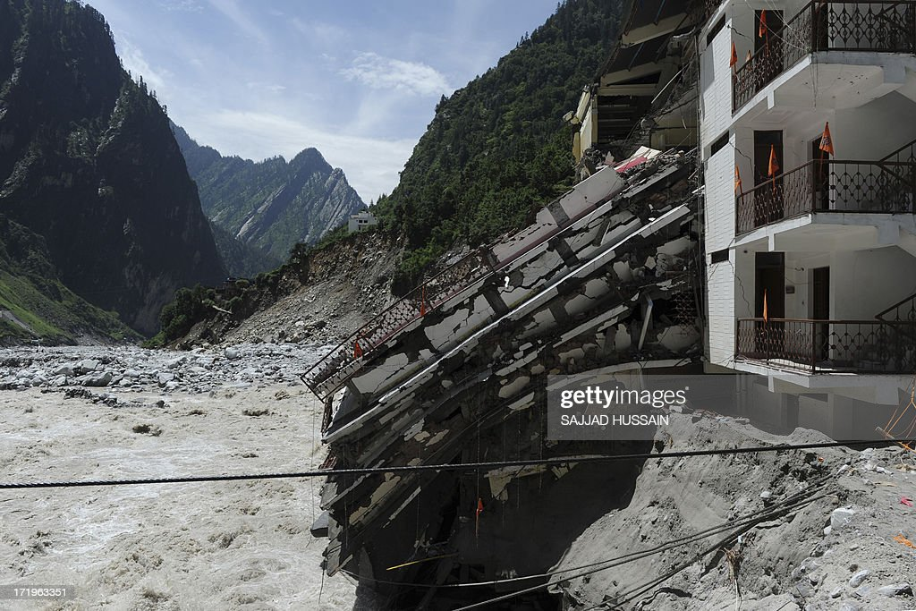A collapsed building lies beside the Alaknanda river in Govindghat following flash floods in Uttarkhand state on June 30, 2013. More than 100,000 mainly pilgrims and tourists have been evacuated from the disaster zone while some 4,000 remain in relief camps after the flash floods and landslides that hit the state on June 15.