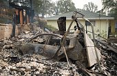 A collapsed garage door rests on a burned out vehicle charred by the Valley fire in Middletown California on September 13 2015 The governor of...