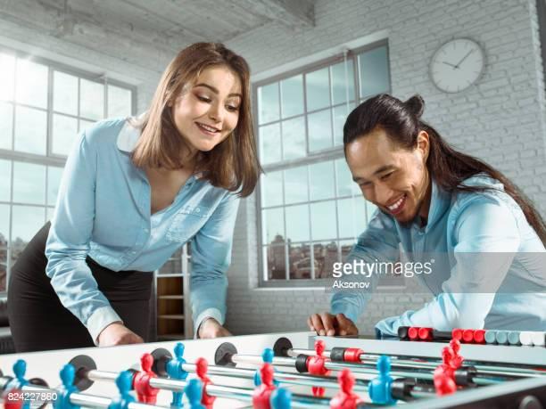 Un collègue enseigne une fille pour jouer au jeu de football/kicker table bureau