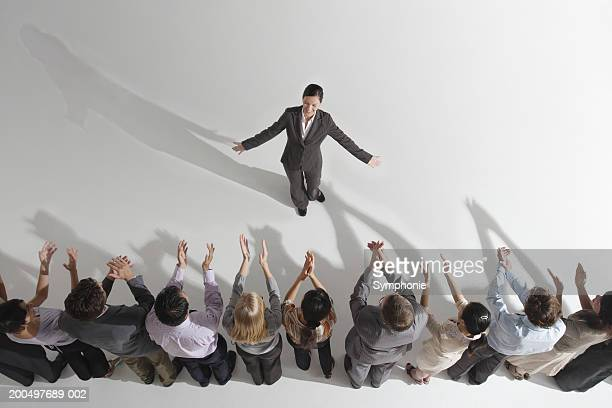 Colleagues applauding businesswoman, elevated view