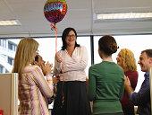Colleagues applauding businesswoman holding 'congradulations' balloon