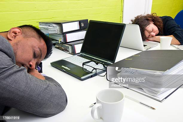 Colleagues asleep at their respective desk