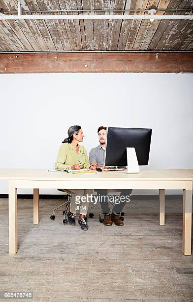 Colleagues at desk behind computer monitor