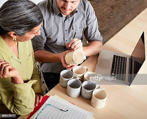 Colleagues at desk discussing pottery mugs