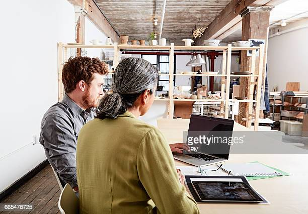 Colleagues at desk in workshop looking at laptop computer