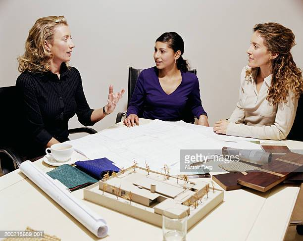 Colleagues at table, by swatches and blueprints