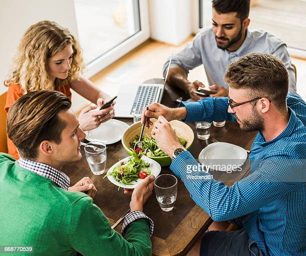 Colleagues at table with cell phone and laptop having lunch