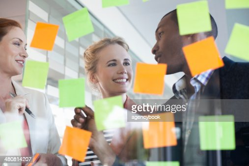 Colleagues brainstorming using adhesive notes