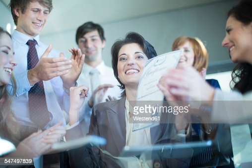 Colleagues congratulating successful businesswoman