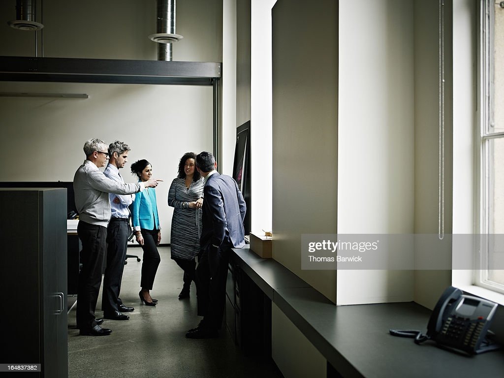 Colleagues discussing project on board in office : Stock Photo