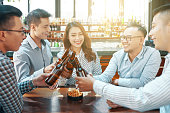 Group of cheerful coworkers drinking beer in pub after work