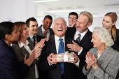 Colleagues giving gift to businessman