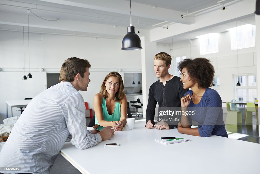 Colleagues having a stand-up meeting at agency : Stock Photo
