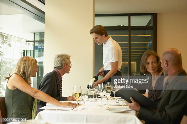 Colleagues having business lunch, waiter showing man bottle of wine