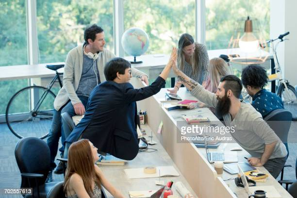 Colleagues high-fiving in casual office